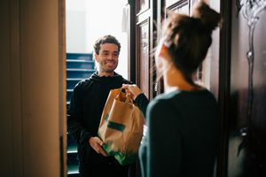 A man having a food delivery to their doorstep, handed over by a woman.