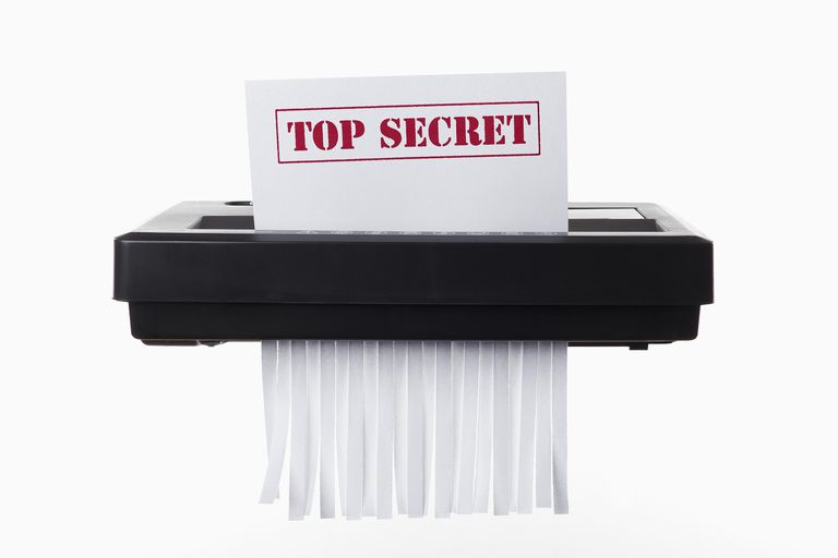 Picture of a top secret document being shredded in a paper shredder