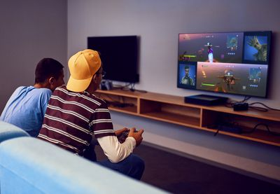 Two male friends sitting on a blue couch playing the Fortnite video game on Xbox One in split screen mode.