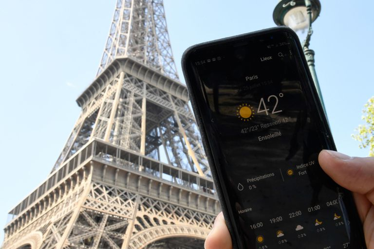 A person standing next to the Eiffel Tower holds a smartphone
