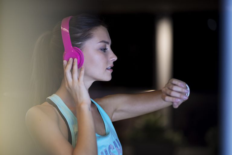 Woman listening to music in headphone via apple watch