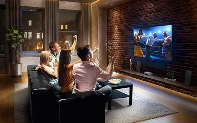 A group of people streaming boxing on a television.