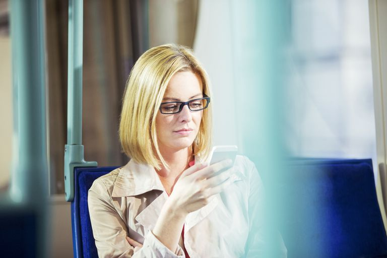 Woman looking at phone on bus