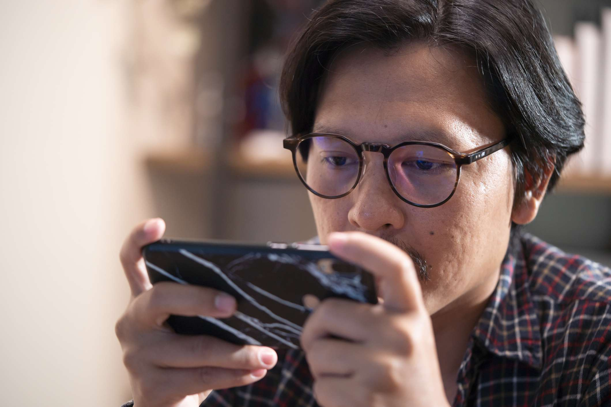 Leisure gamer plays action video game on mobile phone.