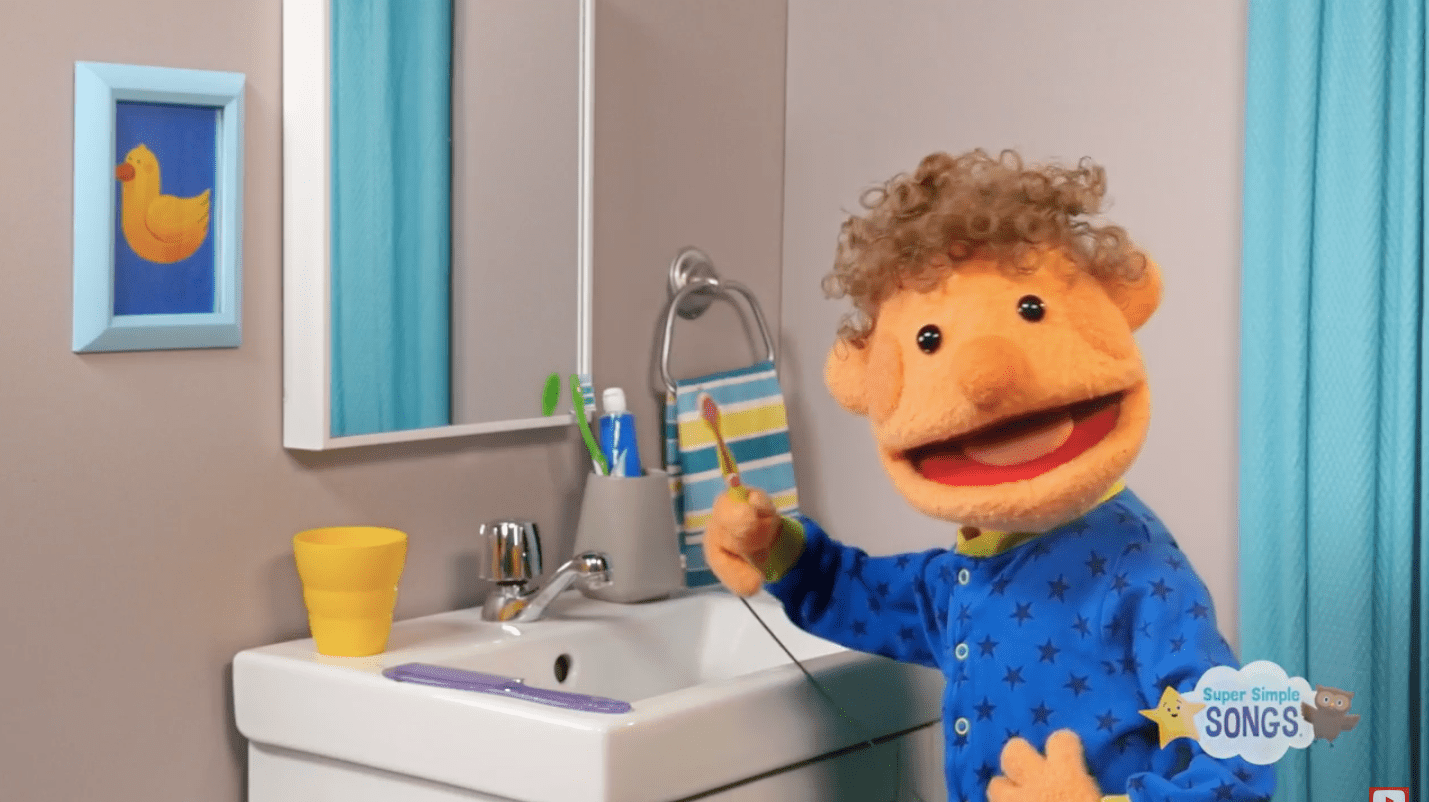 A puppet stands in front of a mirror brushing his teeth.