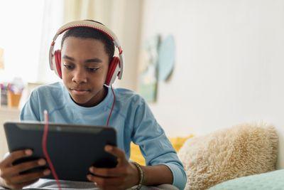 Student wearing headphones using digital tablet