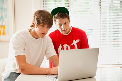 Teen boys working on the computer in the kitchen