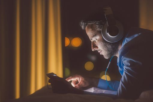 A man sitting in the dark looking at his smartphone with large headphones on his head