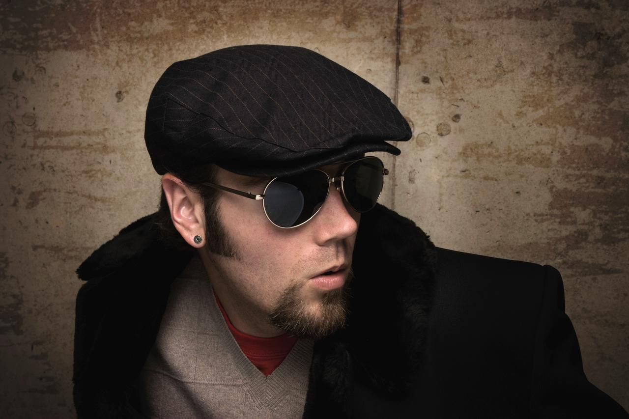 Man with reflective aviator sun glasses and fur collar on trench coat