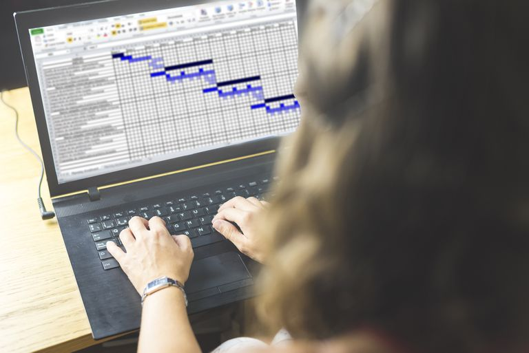Person managing spreadsheet on laptop