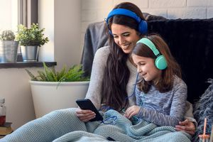 A woman and her daughter wearing headphones and listening to music on an Apple iPhone.