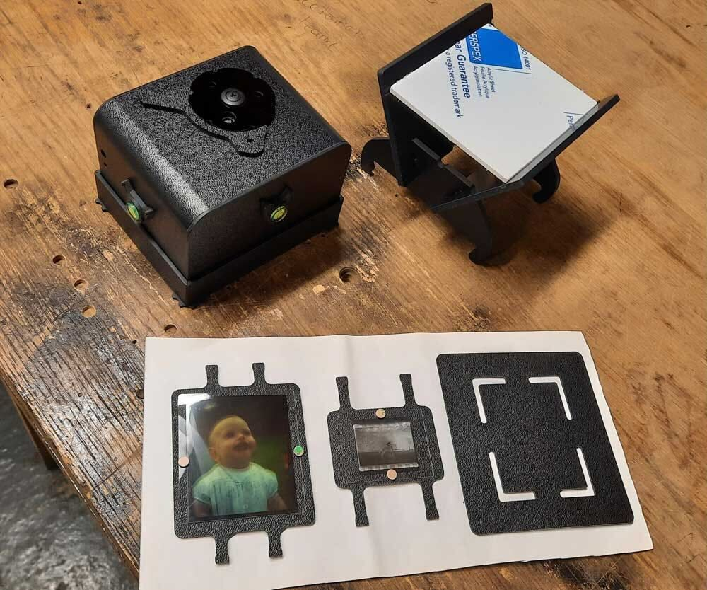 The Pinsta camera body, with photographic film and a developed negative nearby.