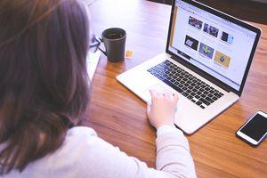 Woman working on laptop with mug of tea