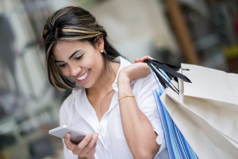 Woman with shopping bags looking at mobile phone