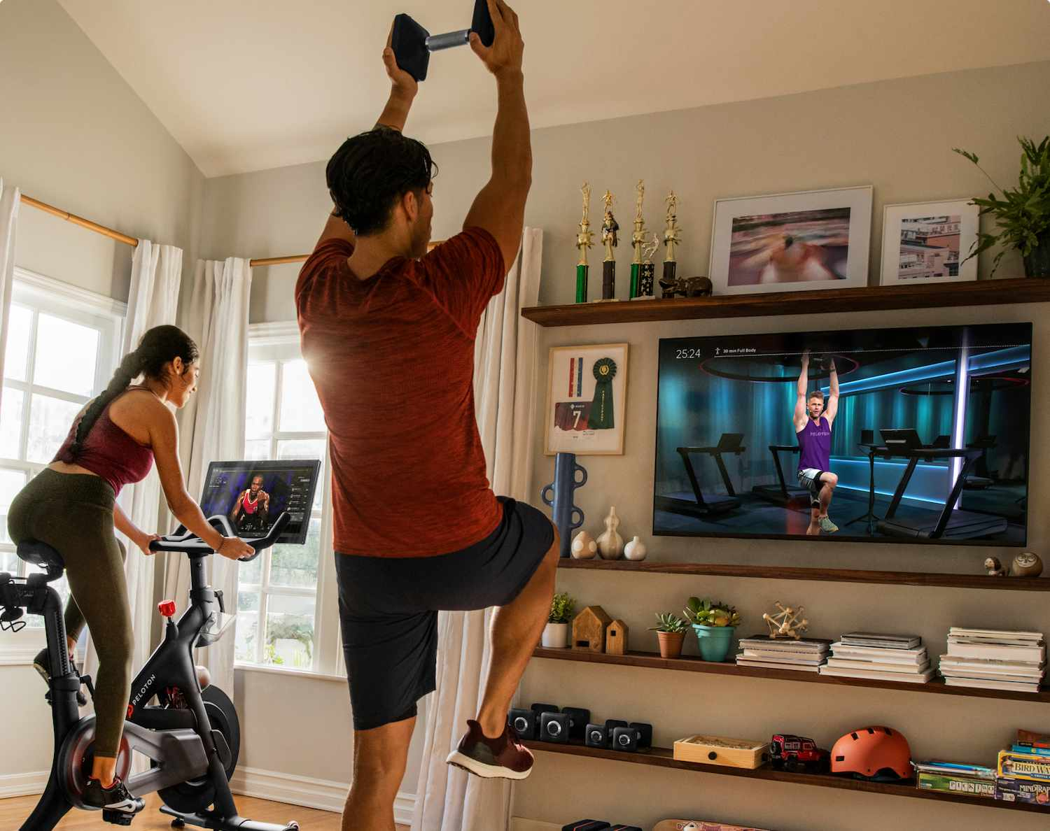 A couple exercising with Peloton equipment