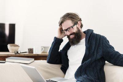 Smiling man looking at laptop