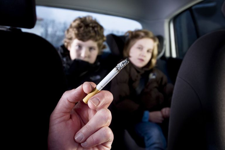 Hand holding a burning cigarette in foreground of car interior with two small children in the backseat