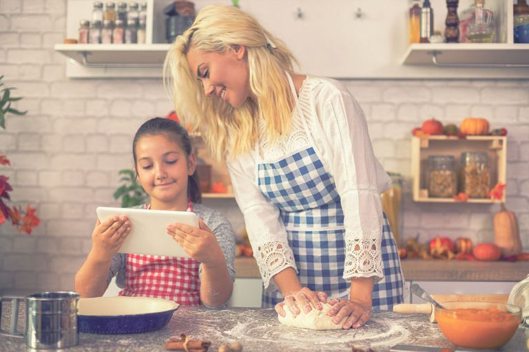 A young girl and her mom in the kitchen on Thanksgiving looking at an ecard on a tablet