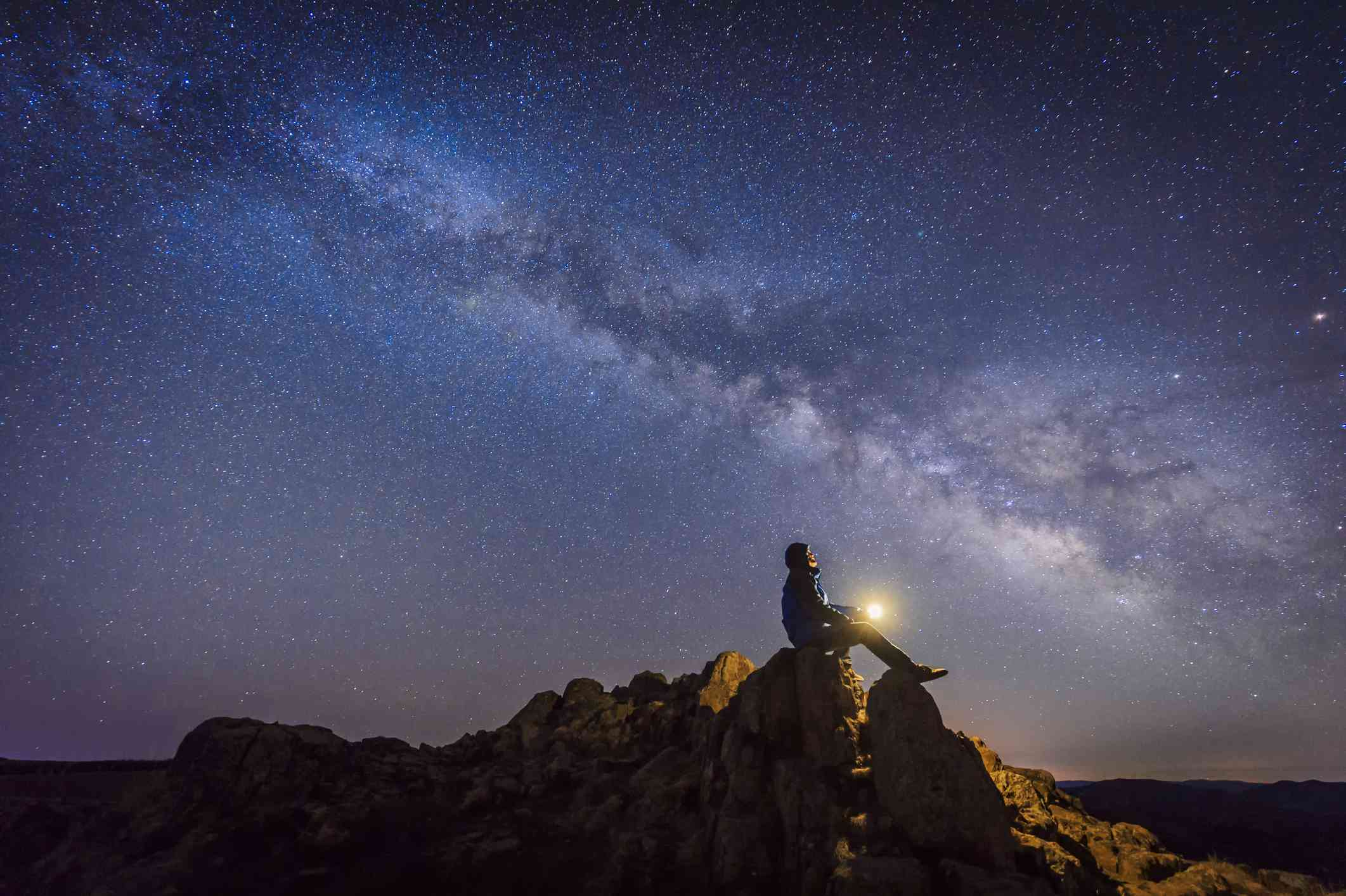 Person sitting under The Milky Way Galaxy with light on their hands.