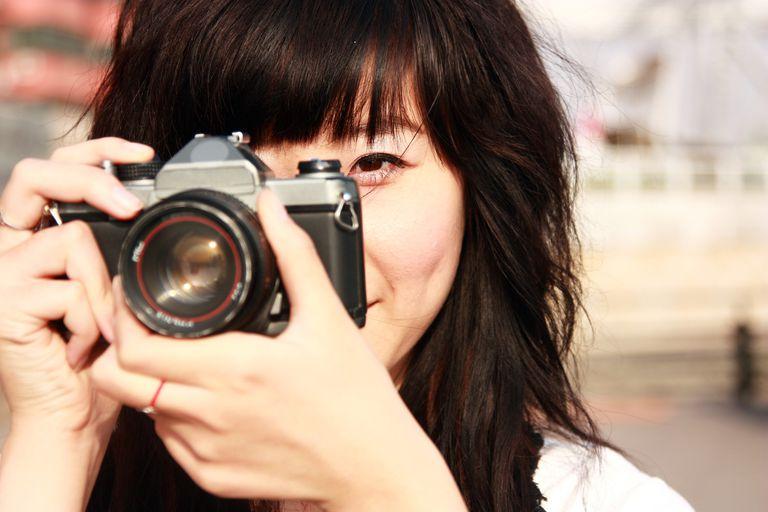 Asian girl aiming digital camera