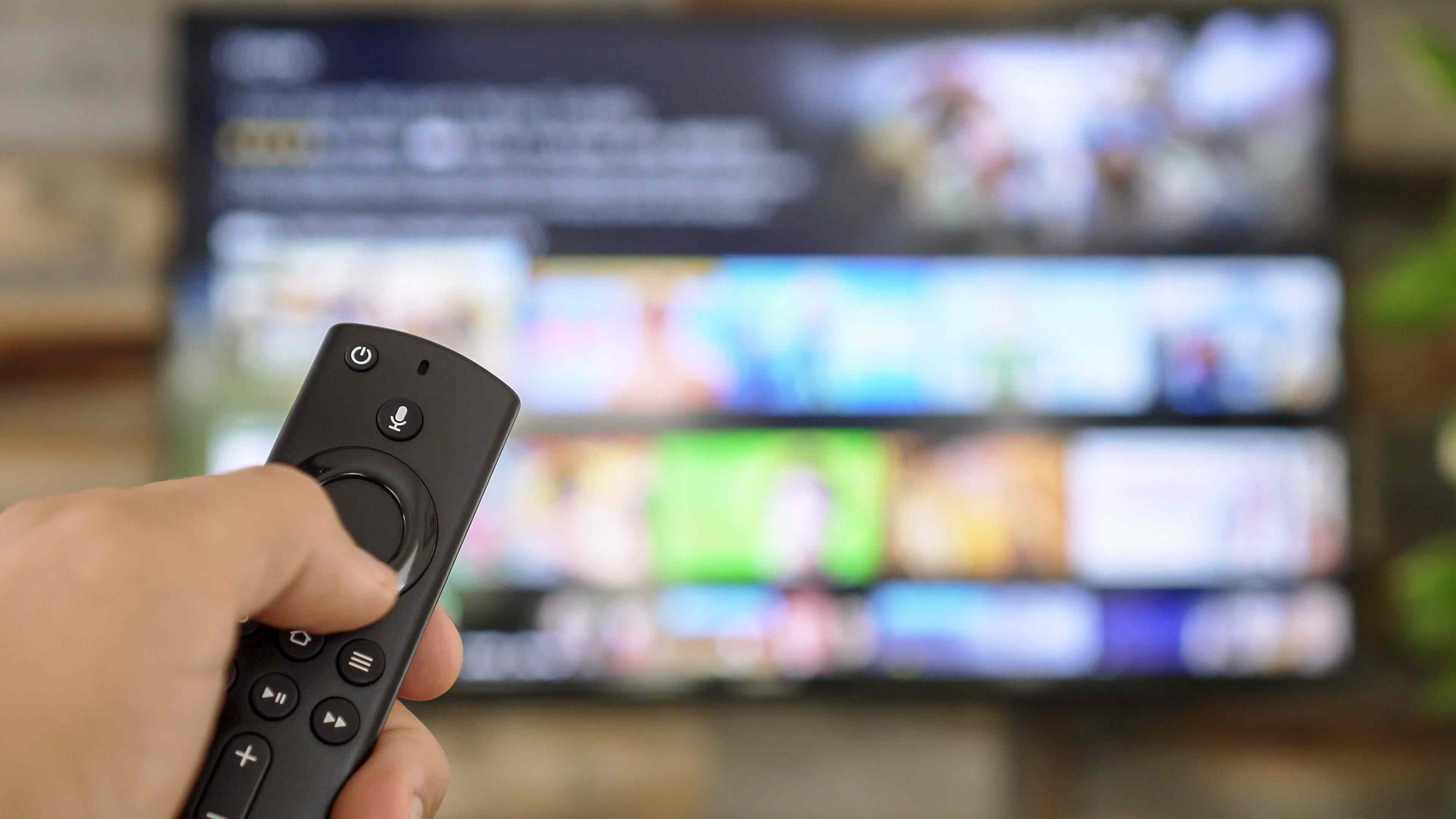 Closeup of a hand holding a remote control with a streaming service on the TV in the background.