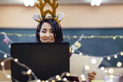 Person in front of computer with Christmas decorations