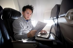 Person using laptop and reading newspaper on plane