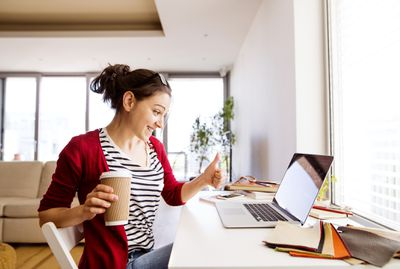 Photo of a woman holding a coffee cup and giving a thumbs up to her laptop screen