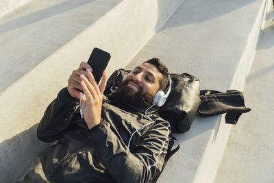 Man lying on his back, listening to headphones and using an iPhone