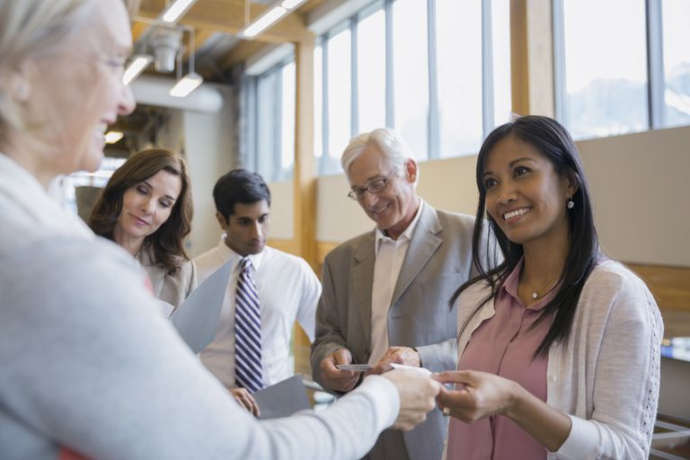 Business people exchanging business cards in office lobby