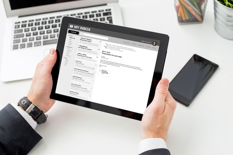 hands holding a tablet showing email