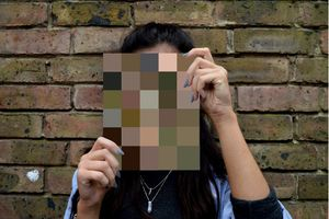 Person holding up blurred image in front of their face