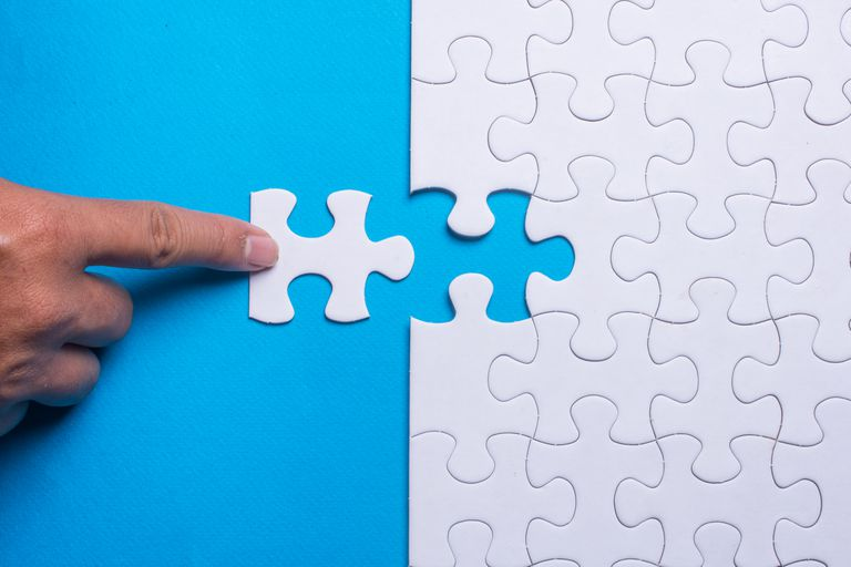 Hand holding piece of white puzzle on blue background. Business and team work concept.