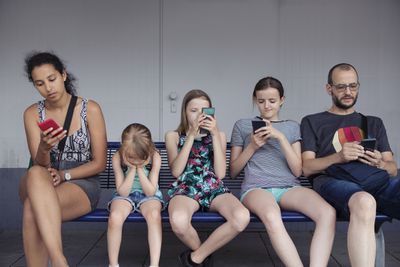 A parent with four children, all of them except the youngest using smartphones.