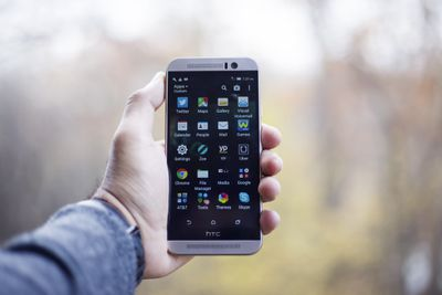 e5cde650ac1 Hand holding an HTC smartphone.