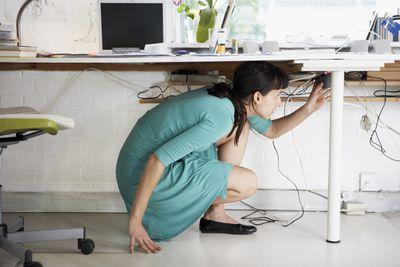 Remote worker adjusting computer cords under desk