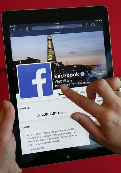 A person uses Facebook on a tablet