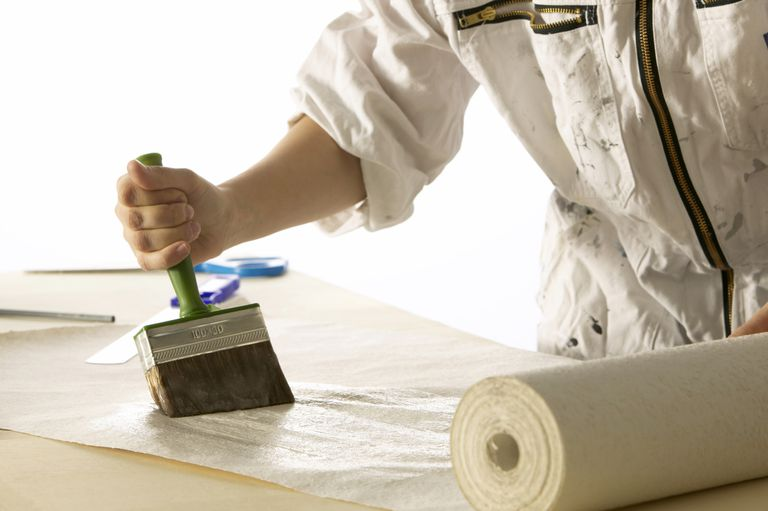 Photograph: person uses a large brush to apply paste to a roll of paper.