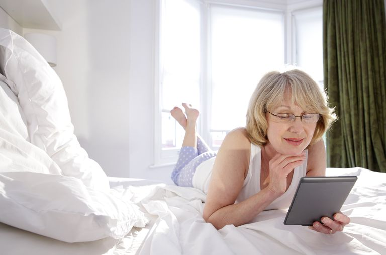 Picture of a woman reading a Kindle on a bed