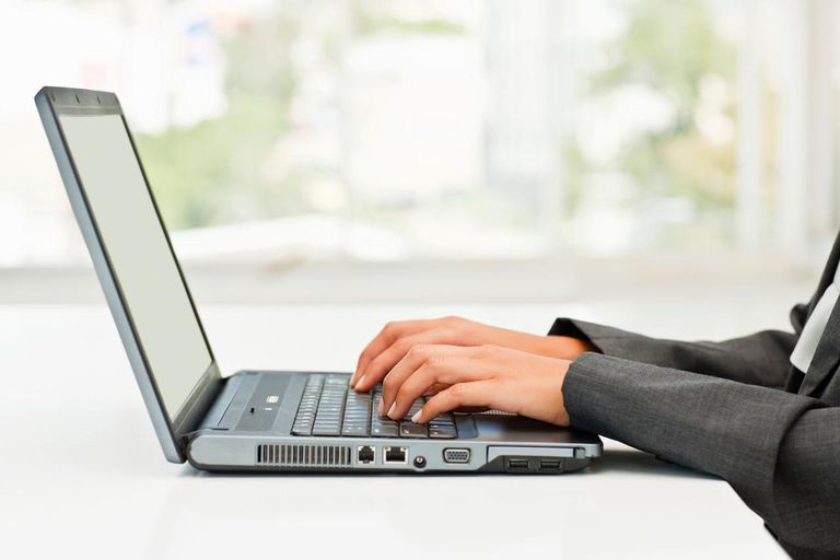 Human hands working on a laptop at desk