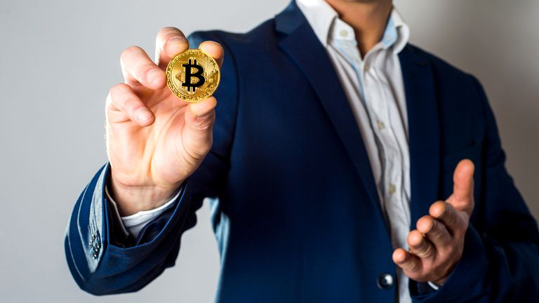 Man in suit holding a Bitcoin coin