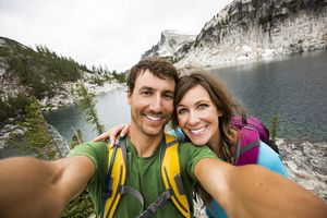 Couple taking selfie next to river with rock forms in background