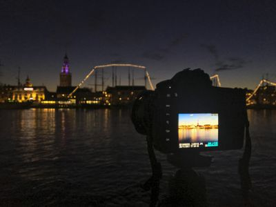 Camera pointed across bay at tower and ships lit up at night