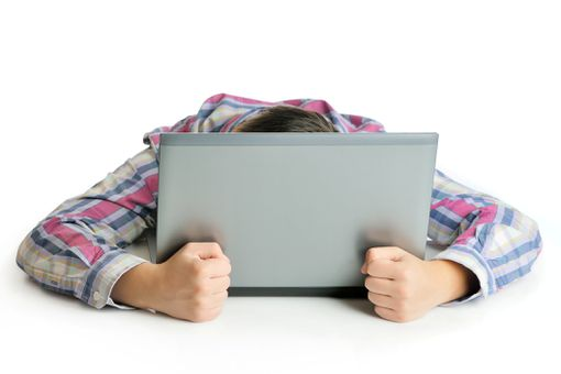 Man with head buried in laptop, fists clenched