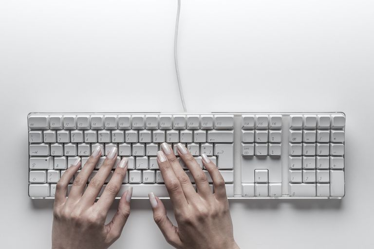Hands typing on computer keyboard