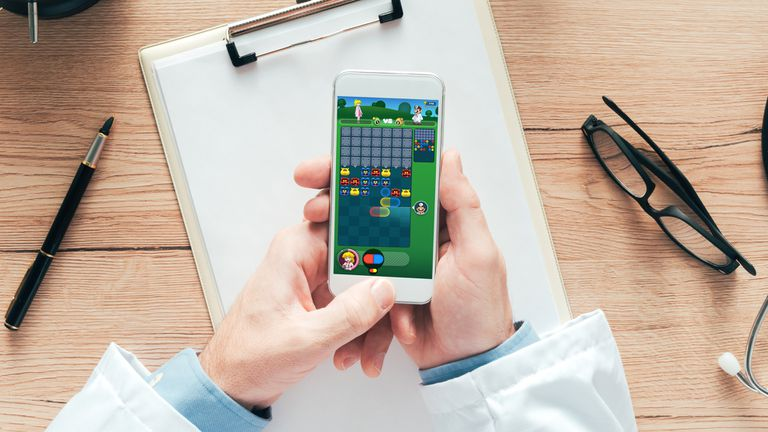 A doctor playing Dr Mario World on an iPhone