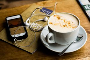A podcast on an iPhone which is sitting on top of a menu near a cup of coffee at a cafe.