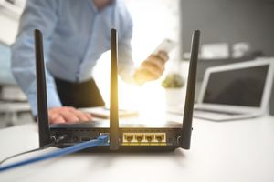 A person in the background with a wi-fi router in the foreground