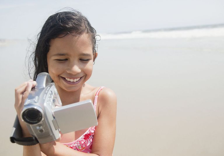 Young girl holding camcorder on beach