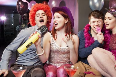Two couples singing while wearing party props and sitting on a couch.
